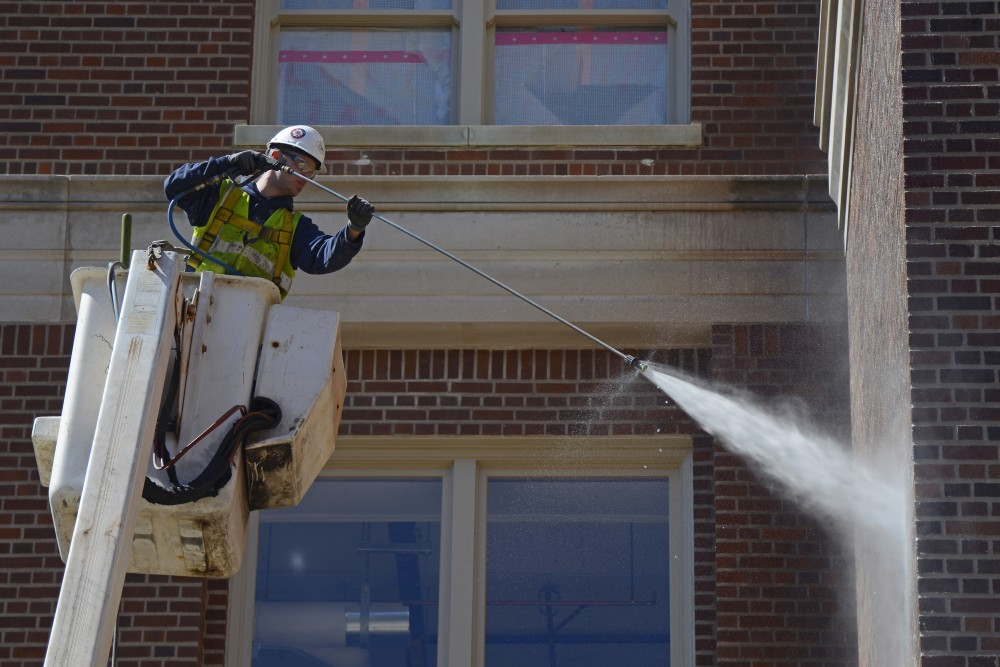 A construction worker power washes the new Tate Laboratory.