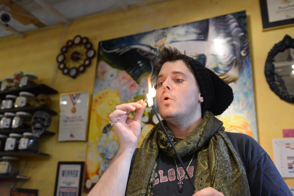 Kyle Reardon lights incense at Magus Books and Herbs in Dinkytown.