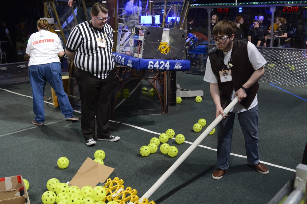 Referee Peter Schneider watches Morgan Matlock reset the playing area during a robotics competition in Williams Arena.