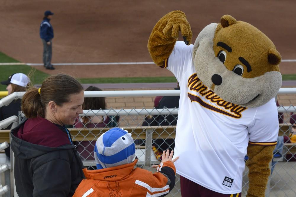 Goldy Gopher fist bumps a young softball fan.