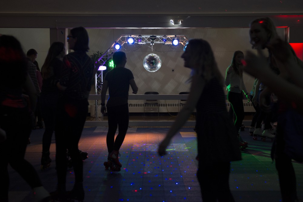 Students roller skate in the Northstar Ballroom at the St. Paul Student Center during a roller disco event.
