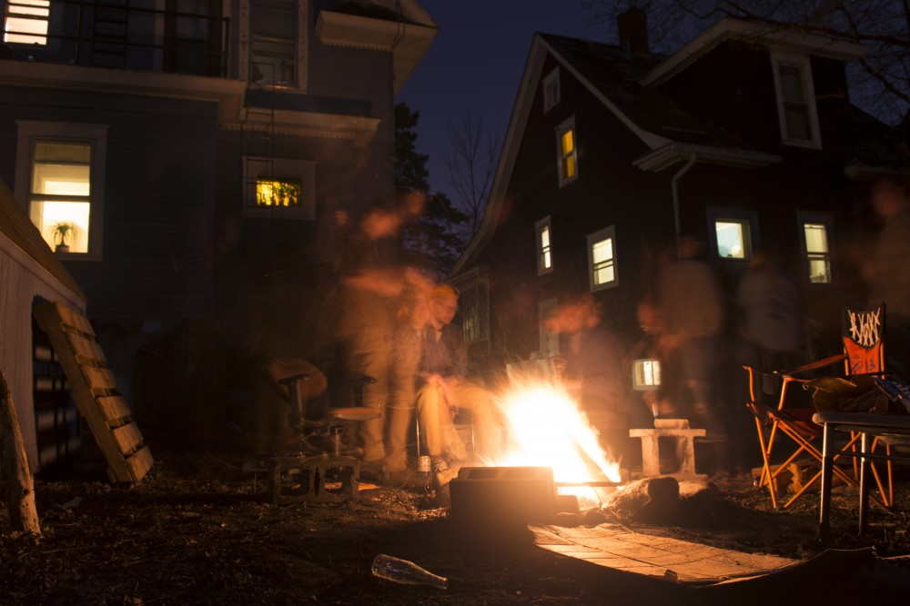 A group of friends gather around a bonfire in the Southeast Como neighborhood.
