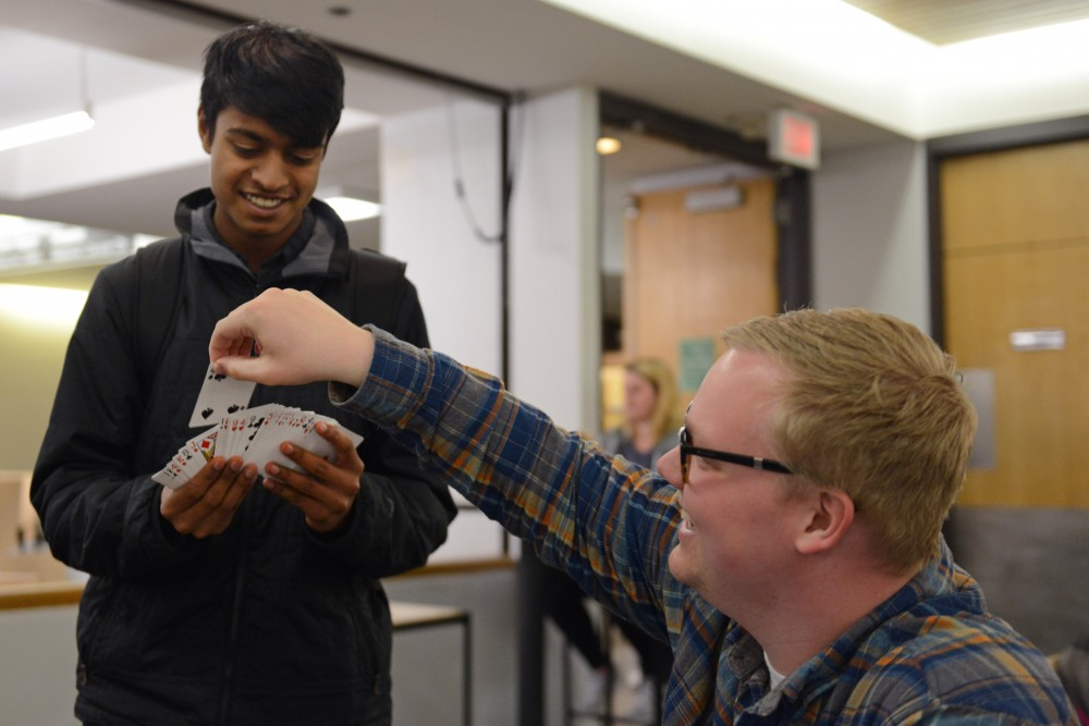 Computer Science freshman Arman Shah performs a magic trick for Neuroscience Senior Cameron Gray in the Molecular and Cell Biology Building on Thursday, April 27, 2017. Shah has been performing for 7 years after teaching himself on YouTube.