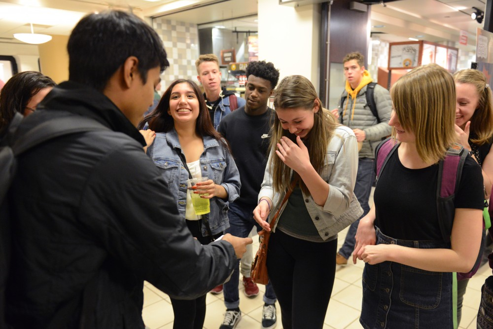Kayla Selbitschka reacts to a trick performed by computer science freshman Arman Shah in Coffman Memorial Union on April 27, 2017.