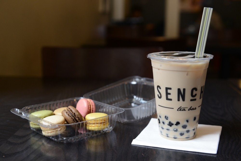 Milk tea with bubbles sits next to macarons on Tuesday, May 30 at Sencha Tea Bar in Stadium Village.