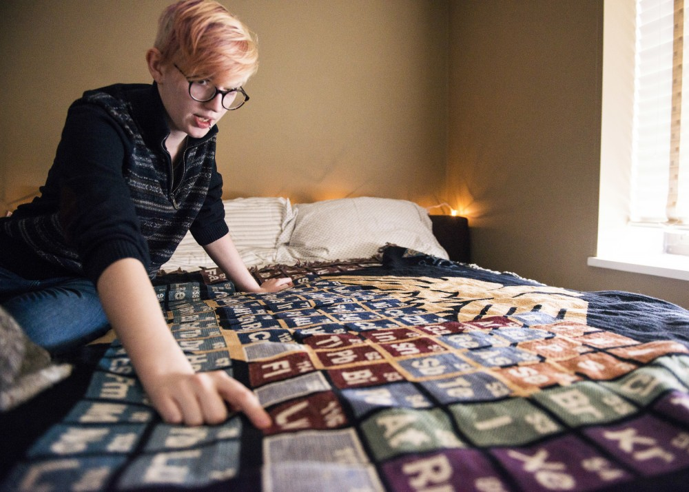 Vee Livermore, who suffers from chronic migraines, drapes their bed with a chemistry-themed blanket. They point to the element Livermorium, named after a distant relative from England.