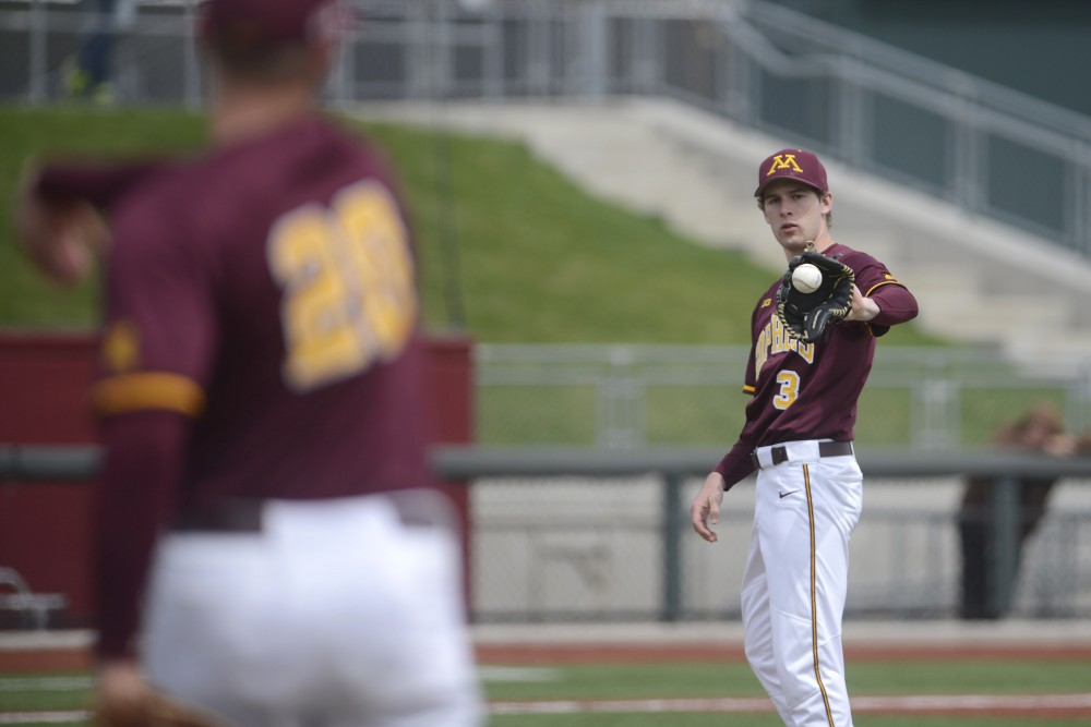 Junior Toby Hanson throws the ball back to pitcher Brett Schulze during the Gopher's game against Illinois on Saturday, April 29, 2017 at Siebert Field.
