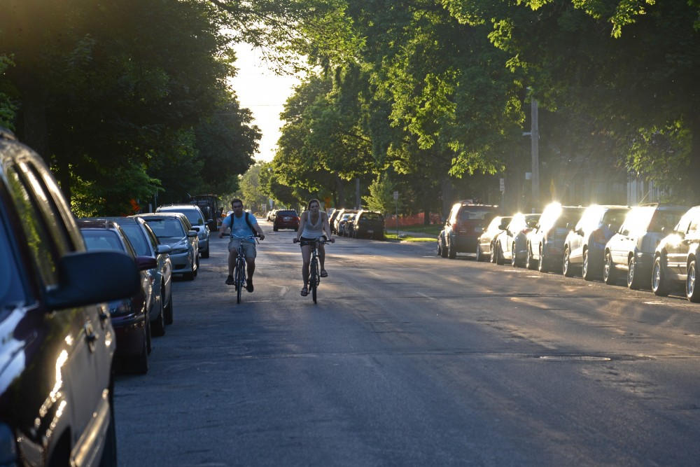 <p>Bikers ride beside crowded parking on both sides of SE 8th Street in Minneapolis.</p>