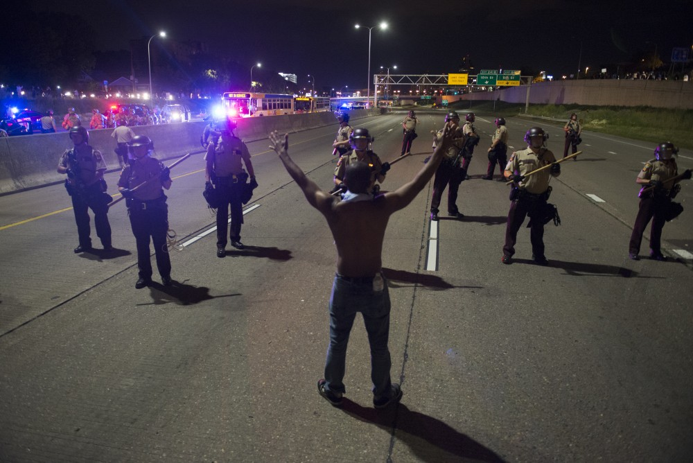 A protestor stands in front of a line of law enforcement officers in St. Paul on Friday, June 16.