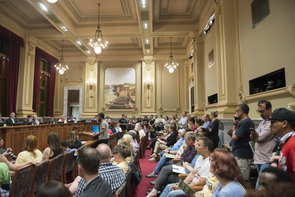 Room 317 in Minneapolis City Hall filled to a capacity of 100 while a public hearing for Minneapolis' proposed $15 minimum wage takes place.