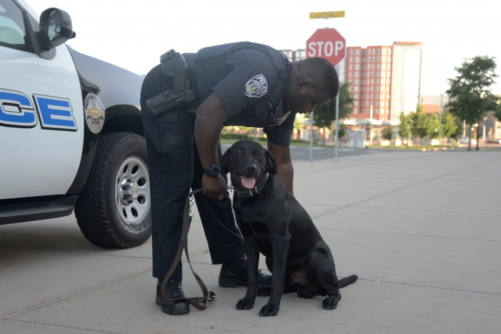 Officer Cunningham brushes his police dog Gator outside TCF Bank Stadium on June 1, 2017. Gator is a specialized bomb dog that is focused on detecting bombs before events on campus.