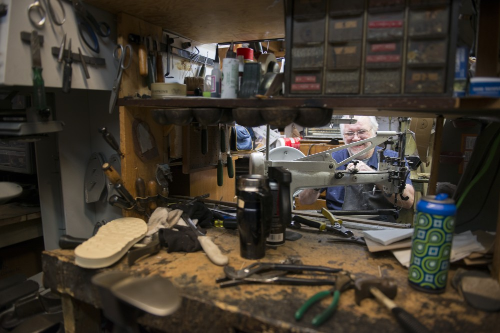 Owner of Fast Eddie's Place Jim Picard works on a shoe inside his repair shop in the Dinkydale building.