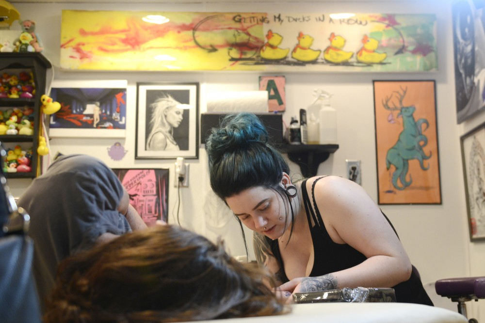 Amy Campbell works on a tattoo at Dinkytown Tattoo on June 3, 2017.