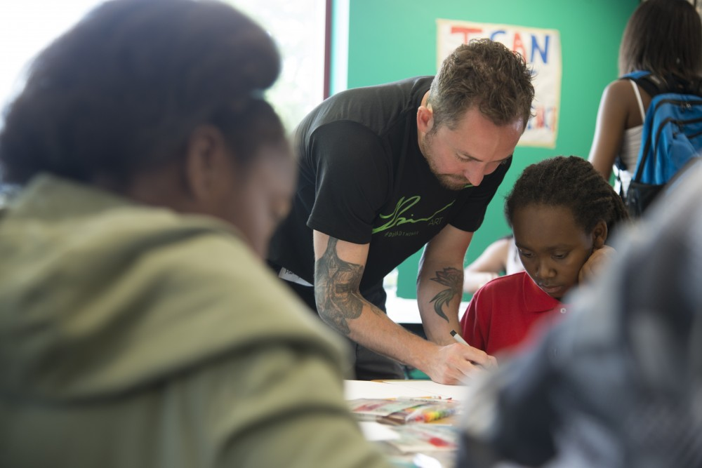 Mark Rivard instructs children how to draw during a workshop on Tuesday, July 11, 2017 at the Harold Mezile North Community YMCA Youth & Teen Enrichment Center. The visual artist runs workshops locally and abroad to inspire children to follow their dreams through experiential learning that points toward art.