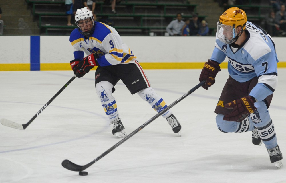 Left defender for the Walser team and former Gopher Ryan Zuhlsdorf carries the puck against left defender for the RBC team Aaron Ness at Da Beauty League on Wednesday, part of a weekly series of games where college and professional athletes come together to play at Braemar Arena in Edina, Minnesota.
