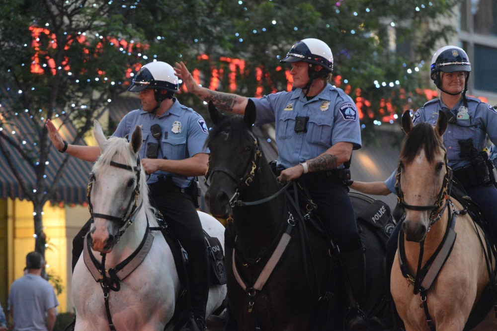 Mounted police participate in the 17th annual CenterPoint Energy Torchlight Parade along Hennepin Avenue on Wednesday.