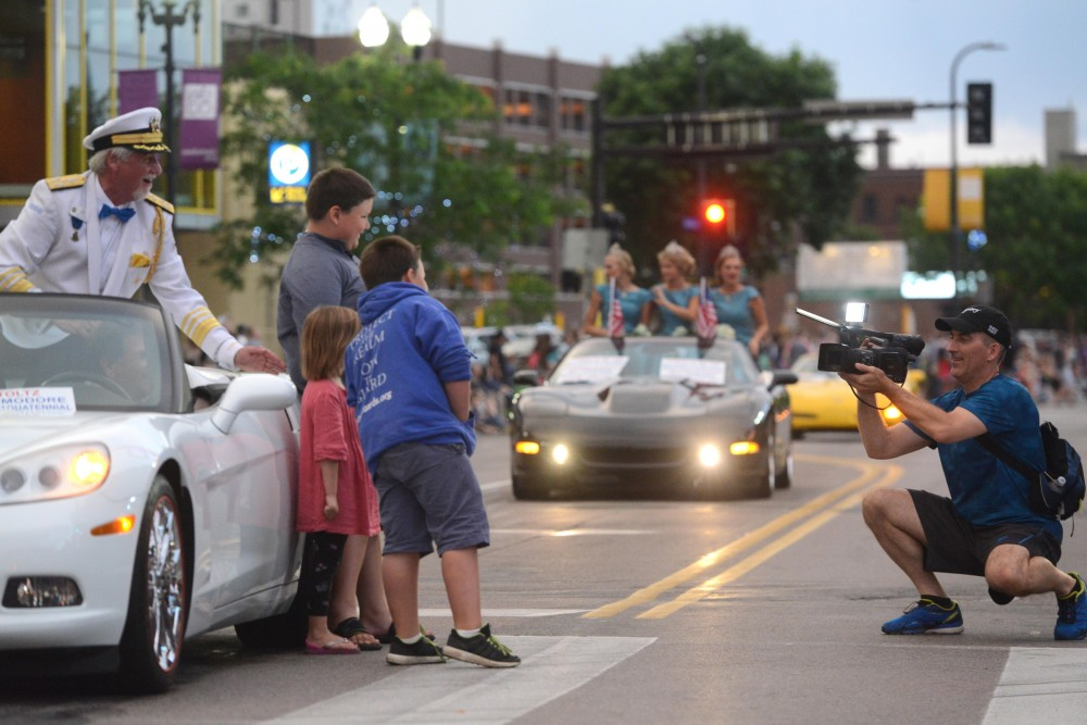 Aquatennial Commodore Dan Stoltz poses with fans in the 17th annual CenterPoint Energy Torchlight Parade along Hennepin Avenue on Wednesday.