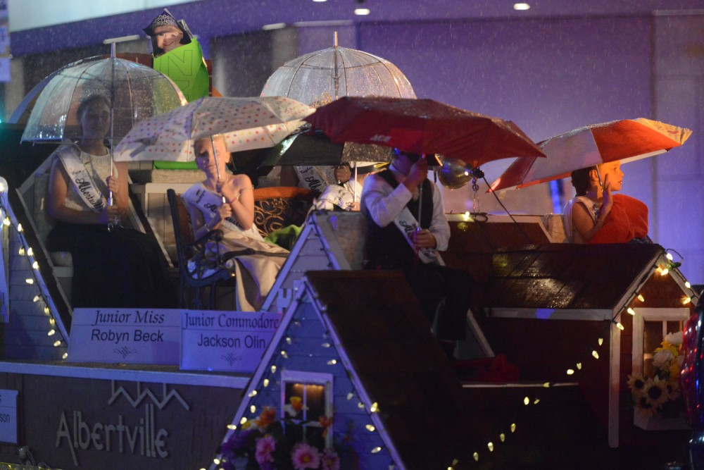 Representatives of Albertville attempt to keep dry as rain pours in the 17th annual CenterPoint Energy Torchlight Parade along Hennepin Avenue on Wednesday.