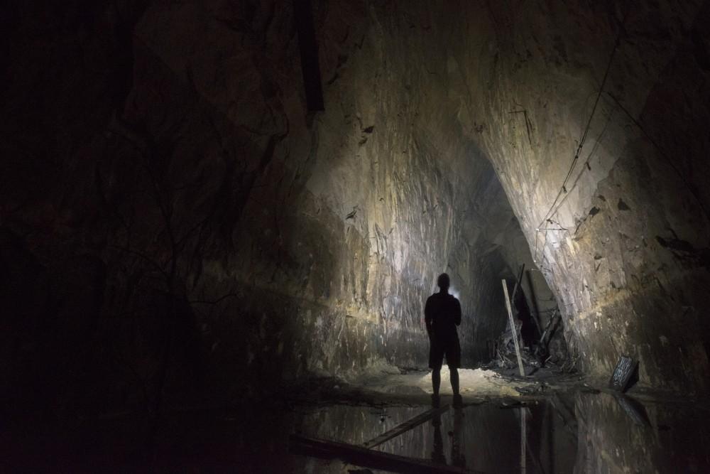A cave explorer illuminates a portion of an underground cave.