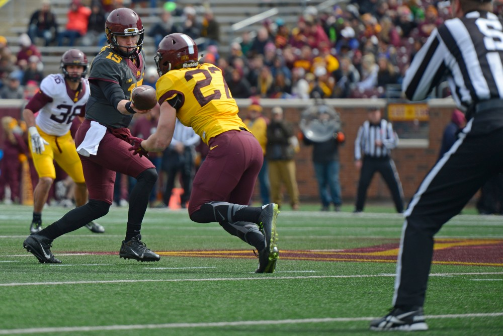 Quarterback Conor Rhoda hands the ball to running back James Johannesson during the Gophers' Spring Game at TCF Bank Stadium on April 9, 2016.