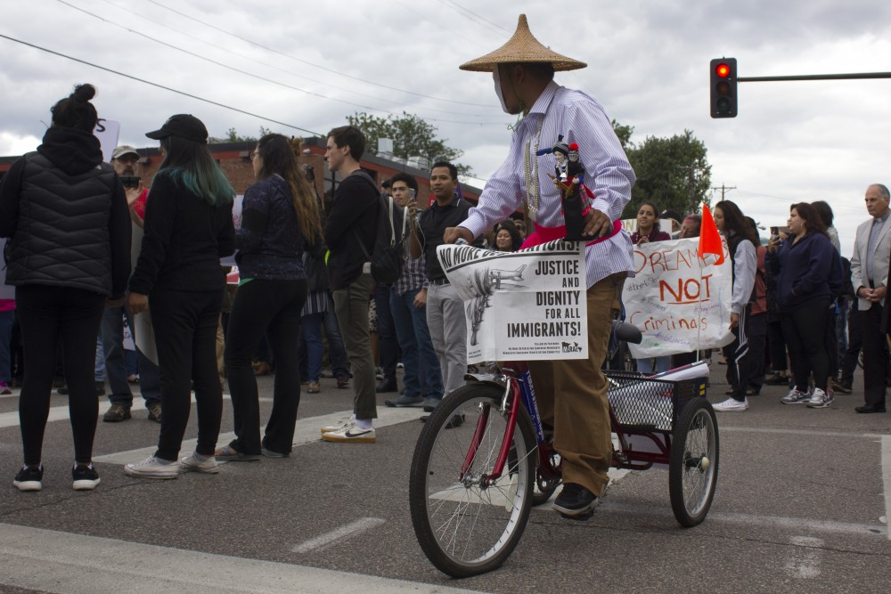 A masked man on a bicycle joined the protest against the repeal of the Deferred Action for Childhood Arrivals policy on Sept. 5 on East Franklin Avenue.