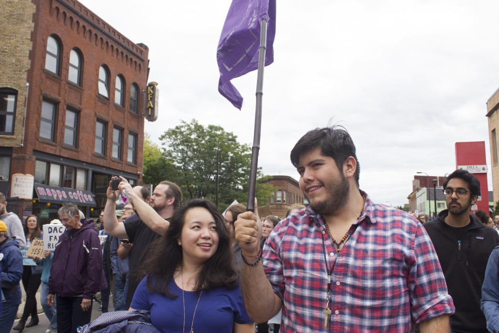 St. Paul resident Eric Bermudez, right, marches down Riverside Avenue with a flag to protest the repeal of the Deferred Action for Childhood Arrivals policy on Sept. 5.