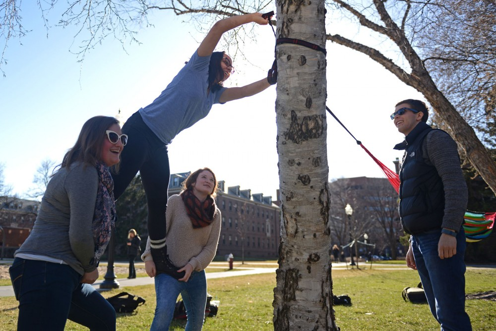 From left, students Laura Darling, Nadja Malby, Alison Gould and Grant Zastoupil hang a hammock outside of Territorial Hall in the Superblock on March 24, 2016.