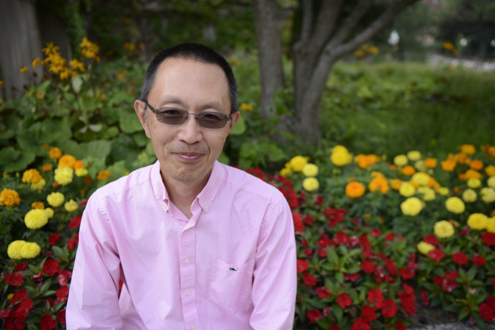 <p>Yoji Shimizu poses for a photo outside Johnston Hall on Friday on East Bank. Shimizu is the new associate dean for graduate education and the director of the Graduate School Diversity Office.</p>