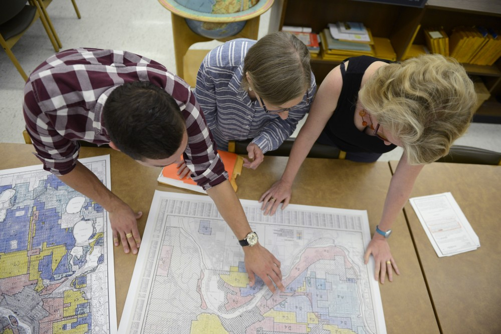 Kevin Ehrman-Solberg, Kirsten Delegard, and Penny Peterson look at city maps that show segregated areas in the metro area at Wilson Library on West Bank on Wednesday August 30, 2017. People like to believe Minneapolis had neither race nor racism, Delegated says.