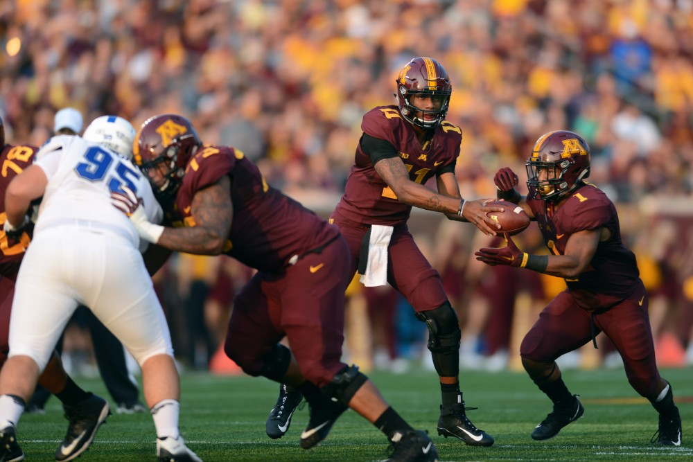Quarterback Demry Croft hands the ball to running back Rodney Smith at TCF Bank Stadium on Thursday, Aug. 31, 2017. The Gophers beat Buffalo 17-7.