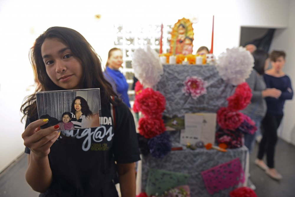 Alma Sanchez holds a photo of her and her mom in front of the Ofrenda that Sanchez helped create at Intermedia Arts in Minneapolis on Thursday, Sept. 28.