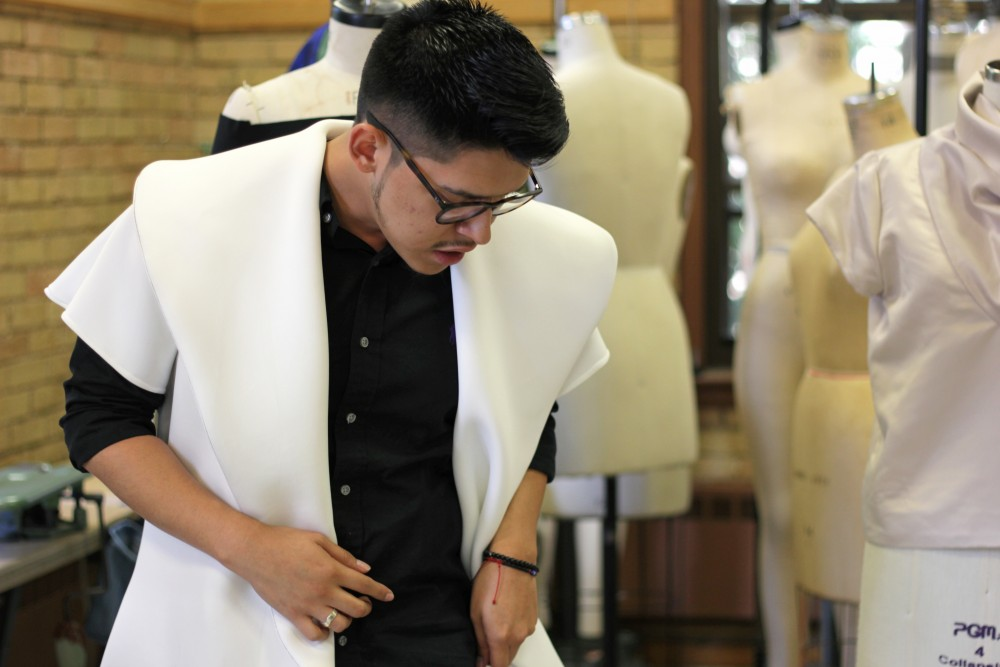 Fashion designer and apparel design major Ivan Gil showcases one of the unisex coats that he designed in McNeal Hall on Friday, Sept. 29.