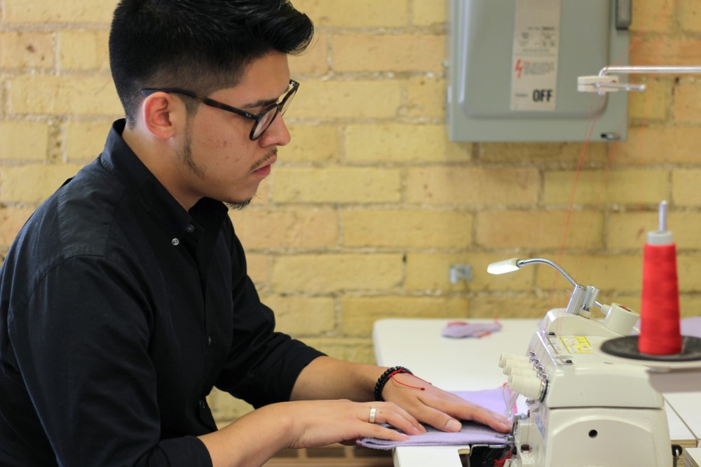 Fashion designer and apparel design major Ivan Gil demonstrates his sewing machine skills in McNeal Hall on Friday, Sept. 29.