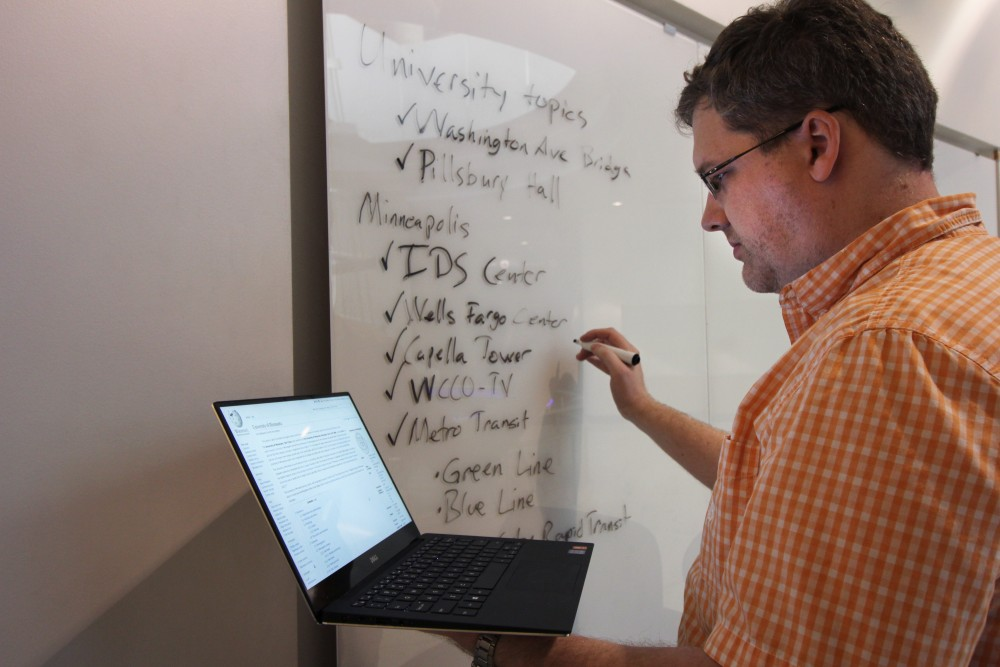 University of Minnesota alumnus and third registered uesr to ever edit the text and photos of the UMN Wikipedia page, Mike Hicks, poses for portraits at Bruininks Hall on Sunday, Oct. 8. The text on the whiteboard represents some of the main topics that he has contributed to.