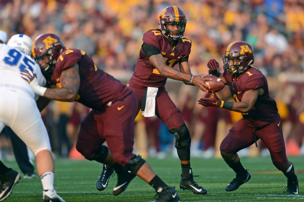 Quarterback Demry Croft hands the ball to running back Rodney Smith at TCF Bank Stadium on August 31.