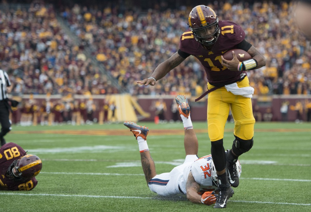 Quaterback Demry Croft gets tripped up at the homecoming game against Illinois at TCF Bank Stadium on Saturday, Oct. 21.
