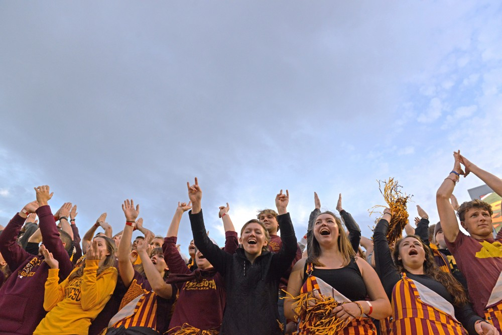 Gophers fans raise their arms to DJ Khaled's