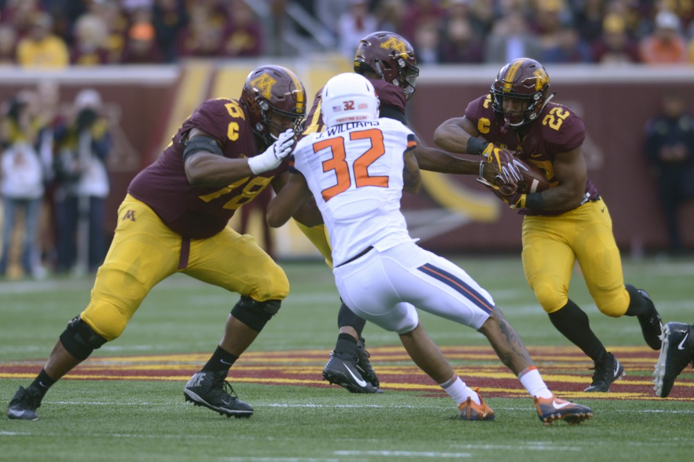 Quarterback Demry Croft passes the ball to running back Kobe McCrary on Saturday, Oct. 21 at TCF Bank Stadium. The Gophers defeated Illinois 24 to 17 at the homecoming game.