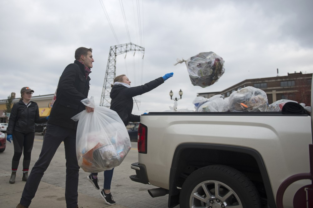 Joseph Scholl and Kelley Bunge throw bags of trash collected in Dinkytown into a pick-up truck on Sunday, Nov. 5.