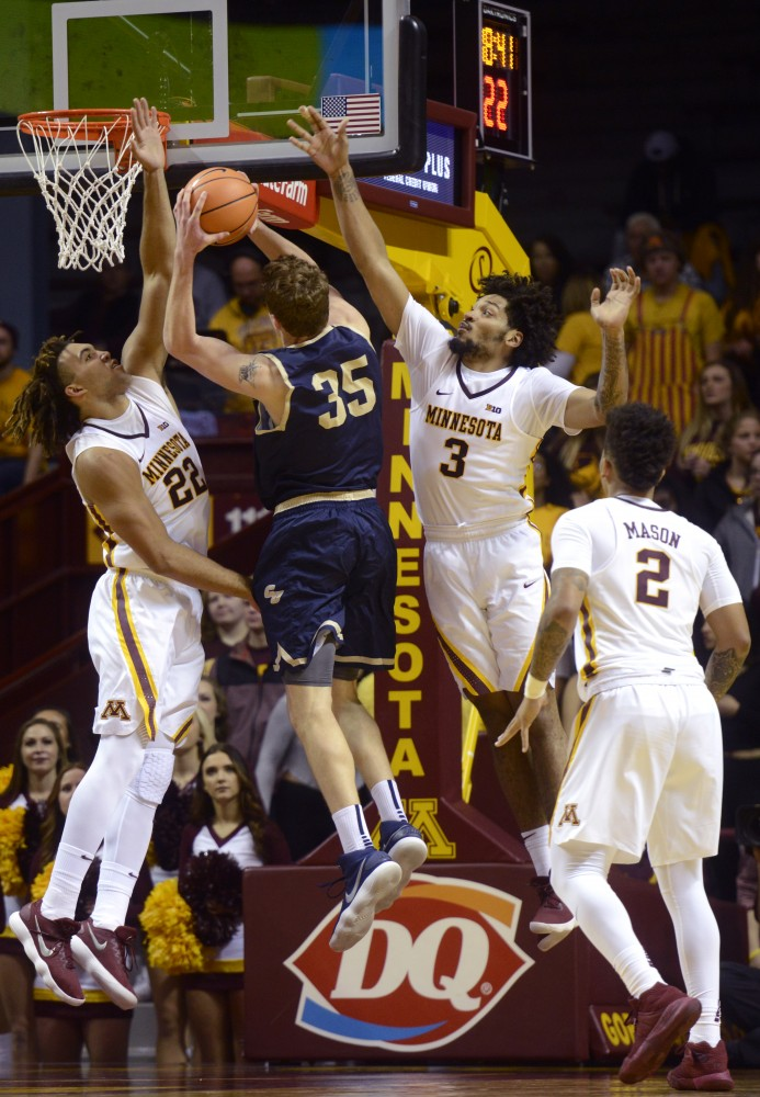Reggie Lynch, left, and Jordan Murphy, right, attempt to block Concordia's shot on Thursday, Nov. 2, 2017 at Williams Arena.