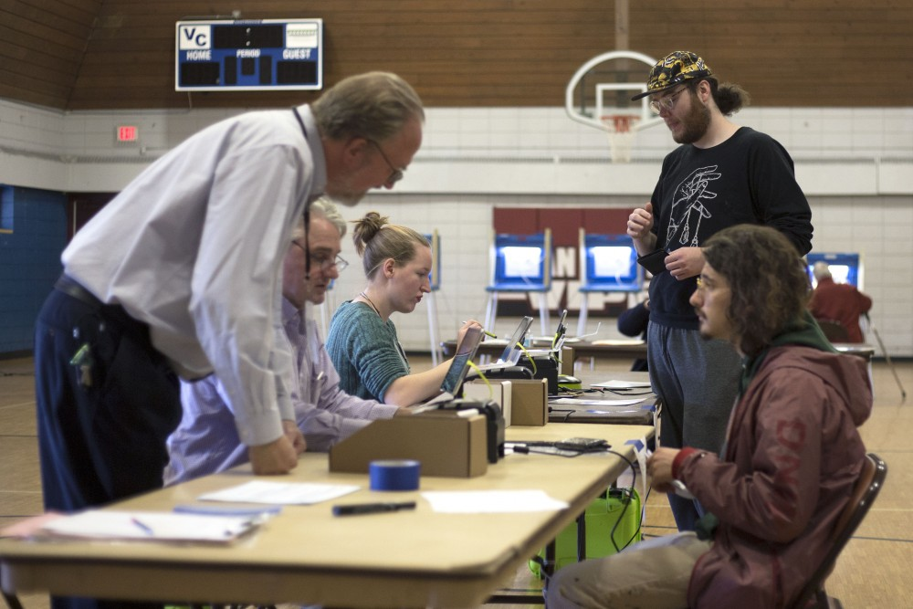 Jackson Willette, who voted for Al Flowers, exchanges information with election volunteers at Van Cleave Park Recreation Center on Tuesday, Nov. 7 in Minneapolis.