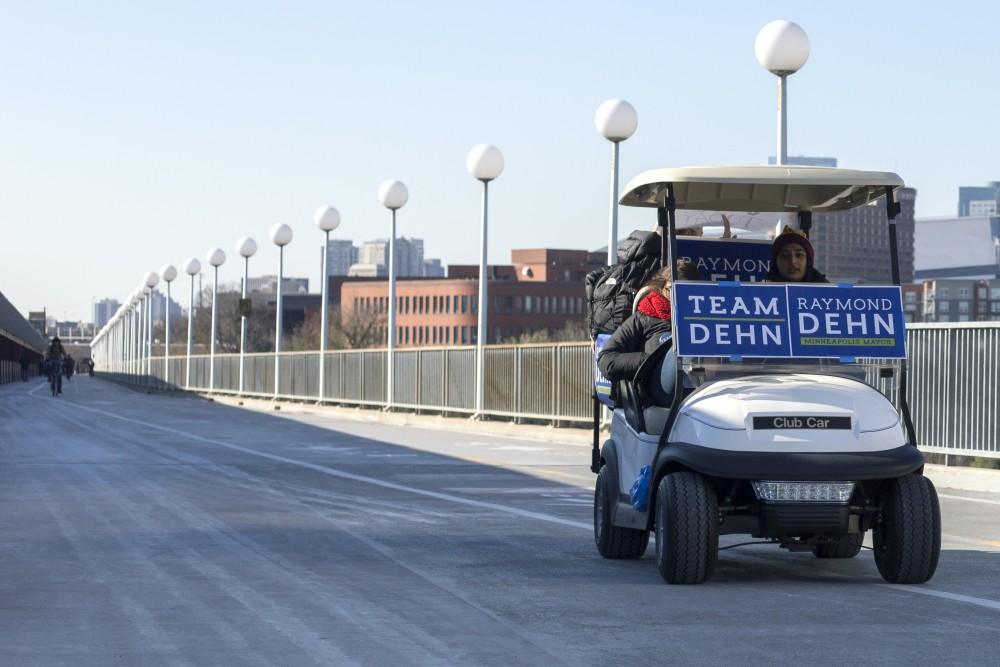 Campaigners for Raymond Dehn, senior Sonia Neculescu and sophomore Aisha Chughtai, offer rides across the Washington Avenue Bridge on Tuesday, Nov. 7 in Minneapolis.