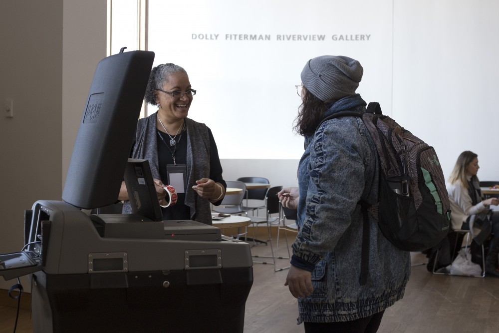 Election judge Mikki Murray speaks with sophomore Melissa Riepe at Weisman Art Museum on Tuesday, Nov. 7 in Minneapolis. Reipe voted for Raymond Dehn, saying she liked his platform page and he seemed the most educated. Murray has been a volunteer election judge since Obama's first presidential election.