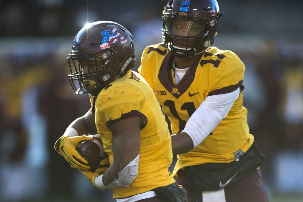 Quarterback Demry Croft hands the ball off to running back Rodney Smith at TCF Bank Stadium on Saturday, Nov. 11.