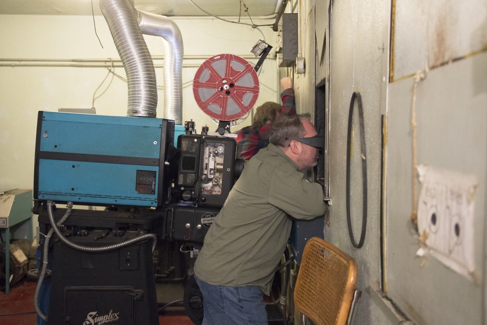 Manager and projectionist Earl Luckes views out a screening window to make sure the movie is playing correctly for the audience at the Parkway Theater on Friday, Nov. 10.