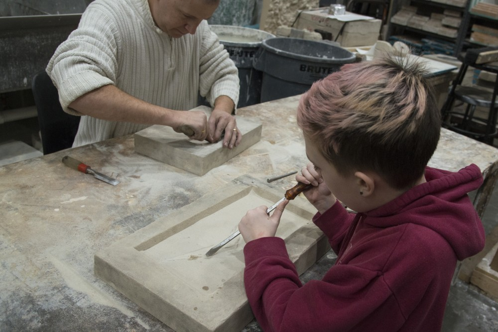 Former assistant landscape professor Tony Siebenaler-Ransom and his daughter, Grae, create a mold design during the Universitys Art Departments 31st annual Iron Pour at the Regis Foundry on Tuesday, Nov. 21.
