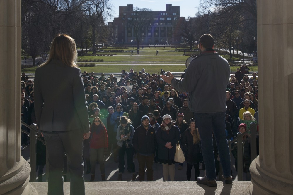 Communications graduate student Kristina Wright, left, and Ecology, Evolution and Behavior graduate student Jake Grossman, right, address demonstrators outside Northrop Auditorium on Wednesday, Nov. 29.