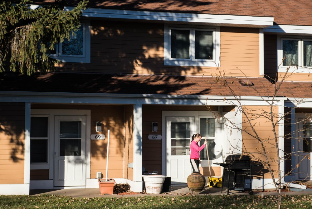 Jackie Smith, 26, burns leaves outside of her apartment just north of the West Bank campus on Tuesday, Nov. 28. Her building is part of a cluster of townhouses that will be undergoing rehabilitation in 2018.