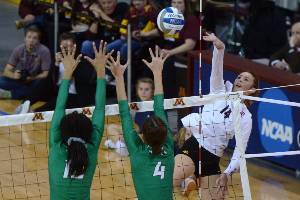 Sophomore outside hitter Brittany McLean falls back from a hit on the Fighting Hawks at Maturi Pavilion on Friday, Dec. 1.