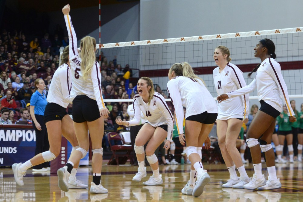 The Gophers volleyball team celebrates scoring a point on the Fighting Hawks at Maturi Pavilion on Friday, Dec. 1.
